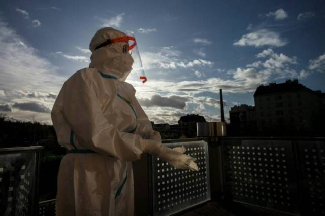 Un soignant enfile sa tenue de protection sur la terrasse d'une maison de retraite de Prague, le 16 novembre 2020 ( AFP / Michal Cizek )