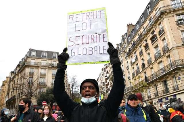 Un manifestant brandit une pancarte appelant au retrait de la loi « sécurité globale» à Paris, le 5 décembre 2020.
