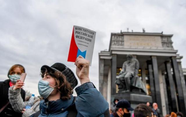 Un partisan de l'opposition tient un exemplaire de la Constitution de la Fédération de Russie, près du monument à la mémoire de l'écrivain russe Fiodor Dostoïevski, devant la Bibliothèque d'Etat, lors d'un rassemblement en soutien à Alexeï Navalny, à Moscou, le 21avril.