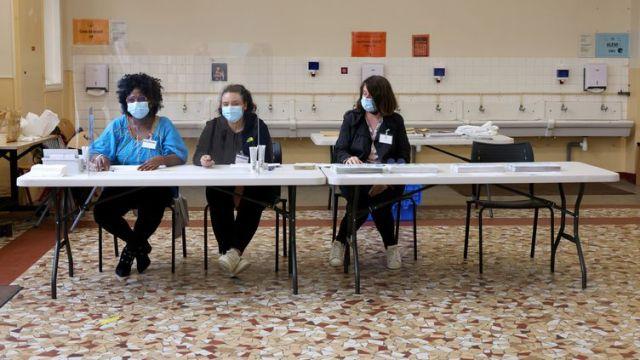 Des assesseures attendent les votants dans un bureau du 13e arrondissement de Paris, lors du second tour des élections régionales et départementales, dimanche 27 juin. (DELPHINE GOLDSZTEJN / MAXPPP)