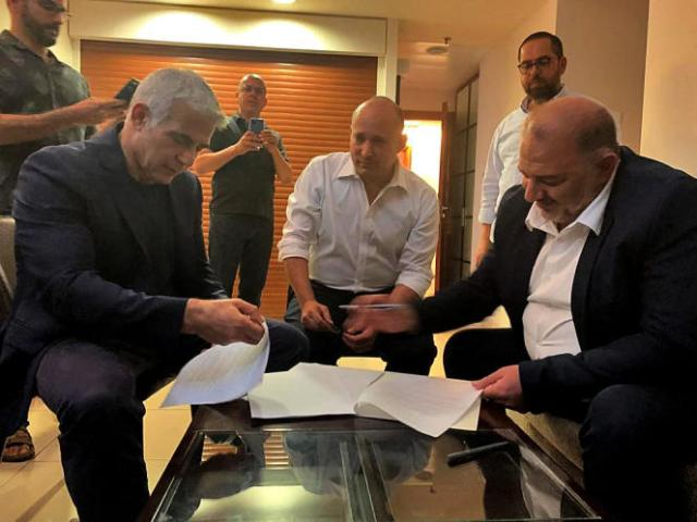 Mansour Abbas (à droite), le chef du parti conservateur islamique, signe un accord de coalition avec le chef de l'opposition israélienne Yaïr Lapid (à gauche) et le leader d'extrême droite Naftali Bennett (au centre) à Ramat Gan, près de Tel-Aviv, le 2 juin 2021. Photo fournie par la Liste arabe unie.