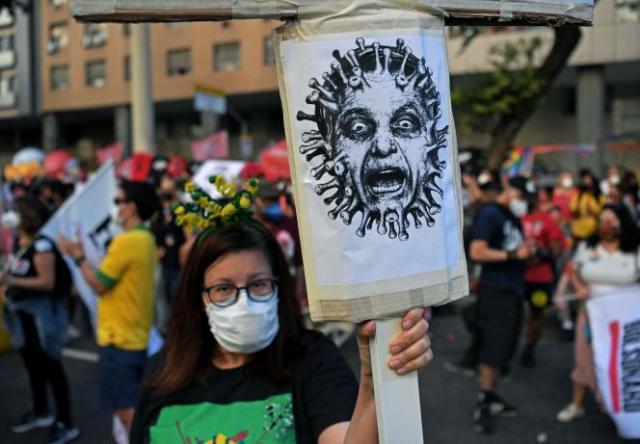Une manifestante tenant un portrait de Bolsonaro habillé en virus, à Rio de Janeiro, le 24 juillet 2021.