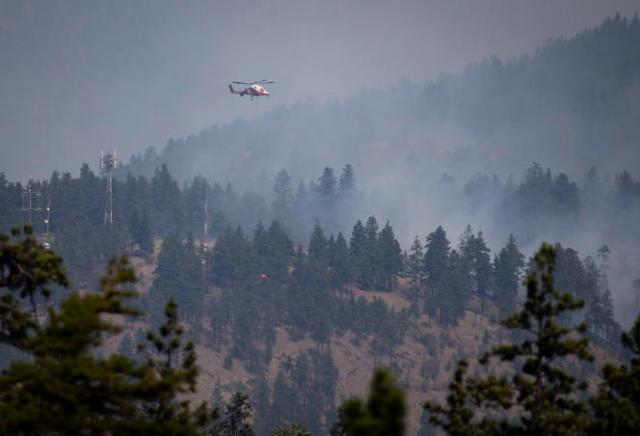 Un pilote d'hélicoptère se prépare à larguer de l'eau sur un feu de forêt à Lytton, en Colombie-Britannique, au Canada, le 2juillet2021.