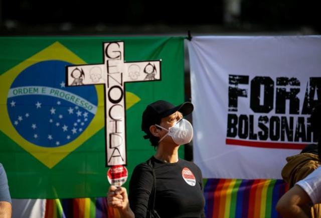 Une manifestante tient un panneau dénonçant un« génocide», lors d'une marche contrele président Jair Bolsonaro, à Sao Paulo (Brésil), le 3 juillet 2021.