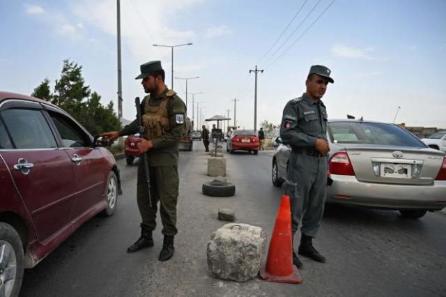 Des policiers afghans à un checkpoint sur une route menant à Kaboul, samedi 14 août 2021.