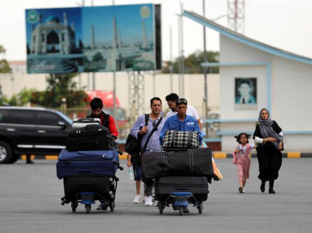 Des personnes quittant Kaboul par l'aéroport, le 14 août 2021.