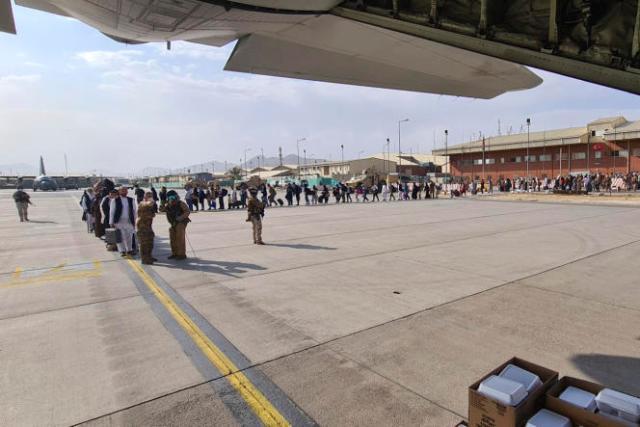 Des passagers attendent sur le tarmac de l'aéroport de Kaboulde monter à bord d'un avion militaire italien pour se rendre à Rome, dimanche 22 août 2021.