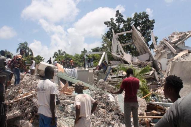 Des habitants fouillent dans les décombres d'un hôtel, samedi 14 août aux Cayes, pour tenter de trouver d'éventuels survivants.