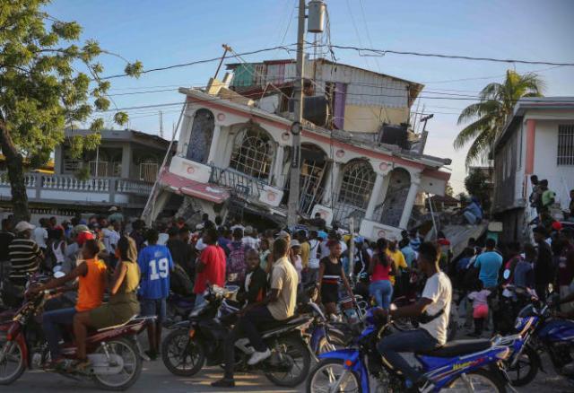 Lors d'un rassemblement devant l'hôtel Petit Pas de la ville des Cayes, détruit par le tremblement de terre survenu en Haïti, samedi 14 août 2021.