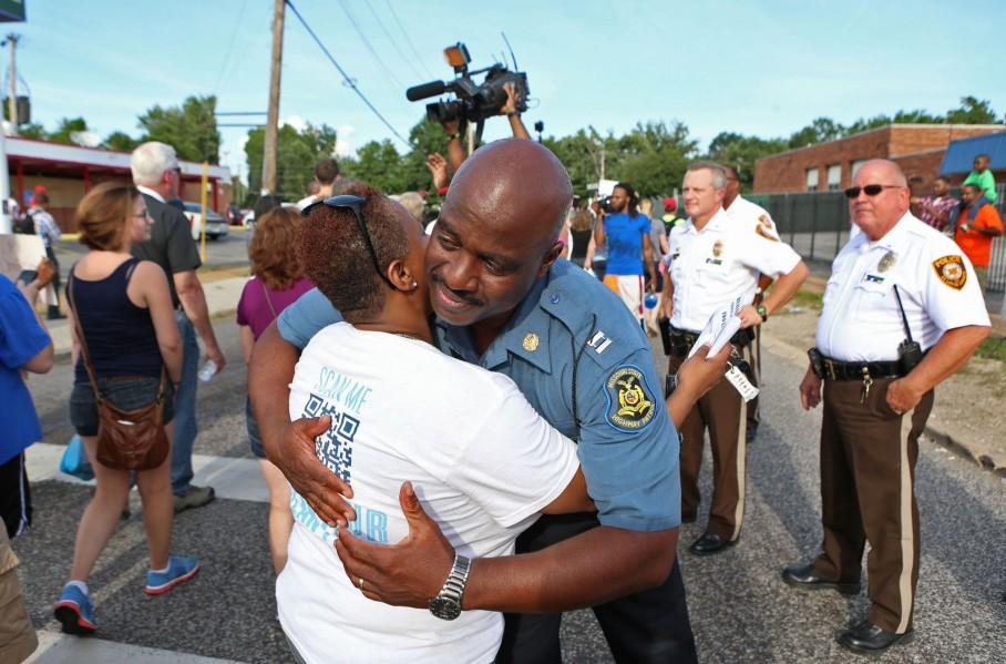 Highway Patrol Captain Ronald Johnson hugs a protester