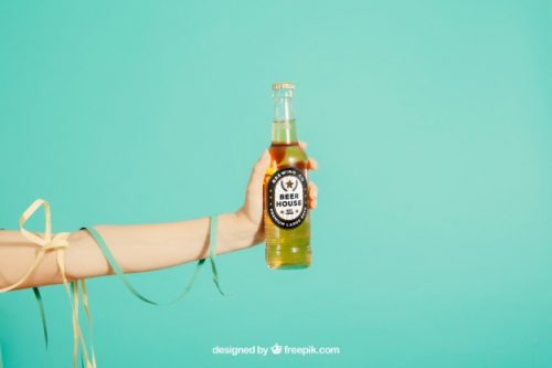 Party concept with arm holding beer bottle Free Psd