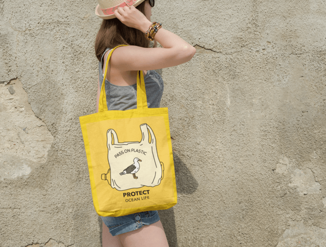 tote-bag-mockup-featuring-a-woman-walking-by-an-old-wall