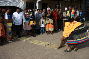 A Zulu bride laying out grass mats for her husband to walk on