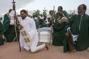 A guard of honour consisting of church officials and the family of Vela Shembe pray during the church leader's send off