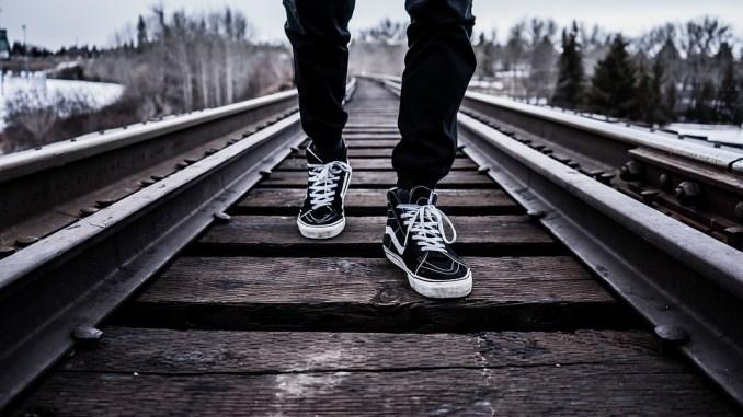 Cammina lungo i binari, con auricolare, per arrivare prima a casa