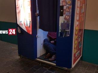 Clochard senza nome dorme dentro cabina delle fototessere, a Perugia