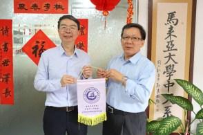 陈奕平教授(左)将纪念品赠予马大中文系代表祝家丰副教授(右)。