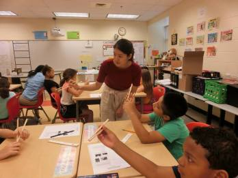 Japanese Outreach Coordinator Mina Uehara teaches 5th graders at Lafayette Upper Elementary school students how to use chopsticks.