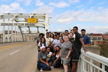 Mehari (near front, leopard-print bandana) poses with UMW students on the Fall Break Social Justice trip to Selma, Alabama, as they begin the emotional trek arcoss the Edmund Pettus Bridge, site of the brutal 1965 Bloody Sunday police attack against civil rights protestors.