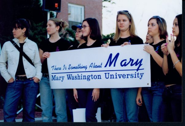 "Borrowing the title from the comedic film, a group of students hold a banner reading ""There Is Something About Mary, Mary Washington University"" at the ""Save the Name"" rally in spring 2004 to protest the proposed idea of eliminating ""Mary Washington"" from the school's name. Photo courtesy of UMW Libraries' Special Collections and University Archives."