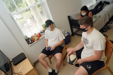 Rugby players Lloyd Stephens of England (with control), Wen Yates of Williamsburg (on bed) and Aidan Hendry of Scotland play video games and follow social-distancing guidelines during Mary Washington Move-In. Photo by Suzanne Rossi.