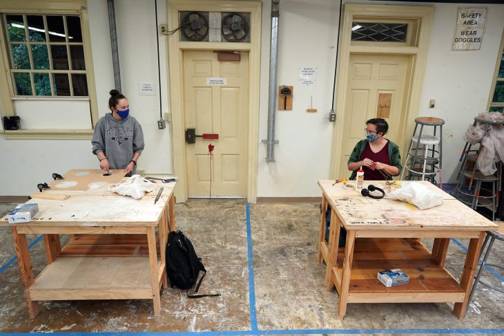 Juniors Katie Ragone (left) and Rebecca Visger (right) chat from their respective workstations during a socially distanced sculpture class in Melchers Hall. Photo by Suzanne Carr Rossi.