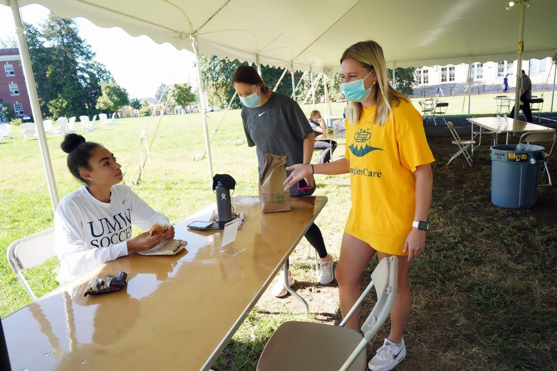 Eagles Care Ambassador Anna Longacher (in yellow) works a shift in a dining tent on Ball Circle. Student ambassadors remind others to follow COVID-19 guidelines. Photo by Suzanne Carr Rossi.