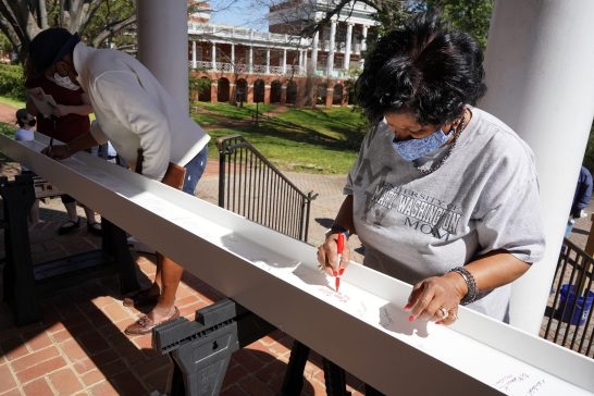 Fredericksburg City Schools Superintendent Marci Catlett, a founder of UMW's James Farmer Scholars program and former adjunct professor, signs her name to a beam that was placed atop Seacobeck. Photo by Suzanne Carr Rossi.