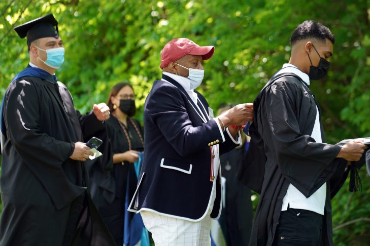 True to tradition, Dean of Students Cedric Rucker adjusts graduates' regalia during one of three Commencement ceremonies for the Class of 2020. Photo by Suzanne Carr Rossi.