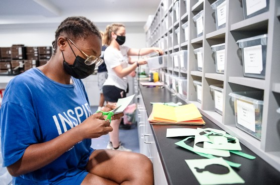 UMW students Noell Evans (front) and Addie Sage (back) create school-spirit-promoting decorations in the basement of the newly renovated Virginia Hall. The room for resident assistants, and their projects and supplies, was freshened up during the 14-month construction period. Photo by Tom Rothenberg.