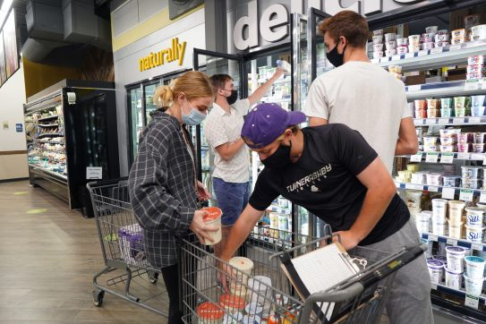 """From left to right: Rebecca Alley, Preston Everett, Cameron Jackson and Dustin Jenkins catalog expired dairy products at the Fredericksburg Food Co-op, as part of UMW's new """"Alleviating Food Waste"""" course. Photo by Suzanne Carr Rossi."""