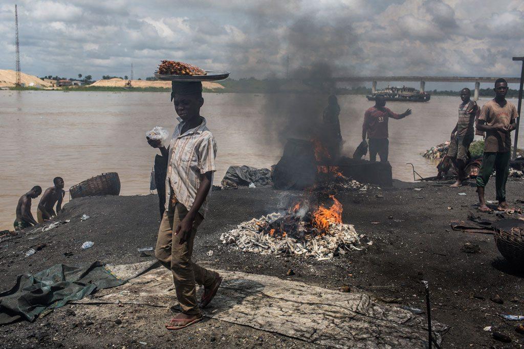 Un niño pasa frene a un punto donde queman basura y materiales de caucho en Yenagoa, Nigeria. Foto: UNICEF/Tanya Bindra