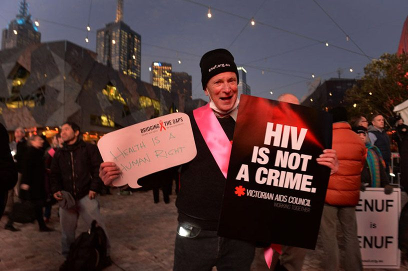 Активит с плакатом «ВИЧ - это не преступление». Фото ЮНЭЙДС