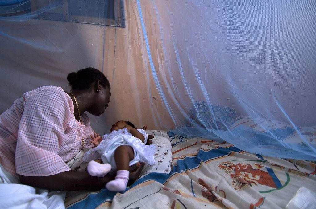 UN photo showing a mother and child protected from mosquito-borne disease by a bednet, the chief tool used in 2015 to prevent malaria transmission in endemic areas.