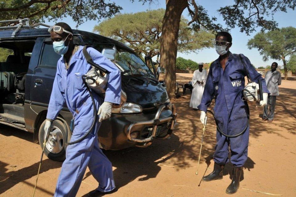 Health workers carrying out a spraying operation to eradicate infected Anopheles mosquitoes which spread malaria