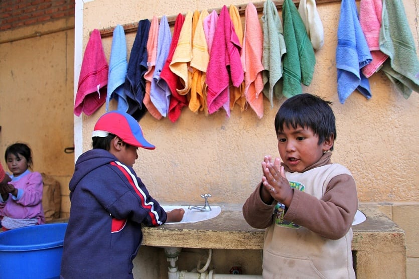 Photo: Two small children wash their hands in Bolivia.