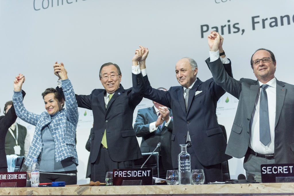 "Photo: On 12 December 2015, the 196 parties to the UN Framework Convention on Climate Change (UNFCCC) adopted the Paris Agreement. Secretary-General Ban Ki-moon (third right) called the negotiations the ""most complicated, most difficult, but most important for humanity."" Also pictured, UNFCCC's Christiana Figueres; French Foreign Minister Laurent Fabius and President of the UN Climate Change Conference (COP21); and French President François Hollande (right). UN Photo/Mark Garten"