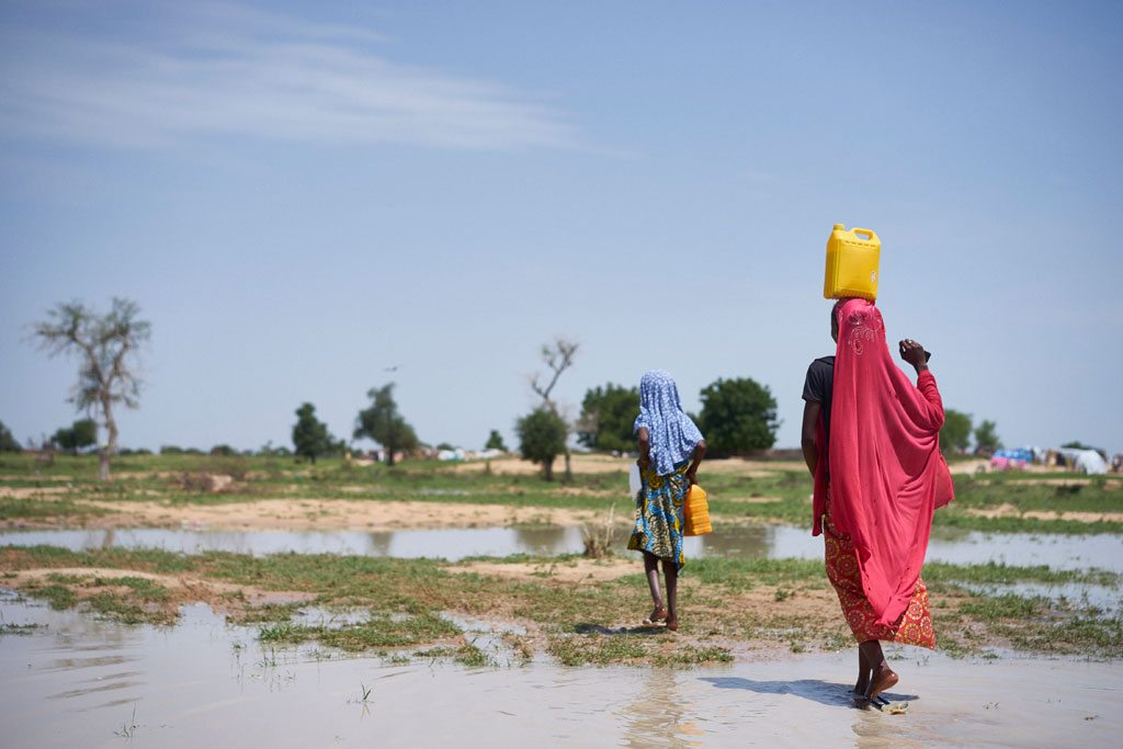 Photo: Girls carry water through a field after rain at a site of displaced civilians in Diffa, Niger, on 18 August 2016.