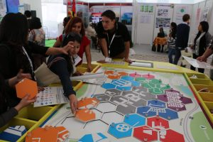 Photo: Habitat 3 attendees play with an SDG puzzle at the Germany booth at the Exhibition Hall.