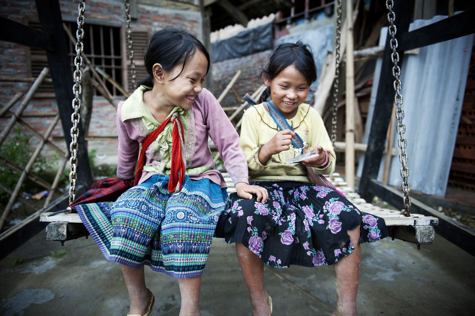 Little girls from a local hill tribe laugh on a swing set in Sapa, Viet Nam.