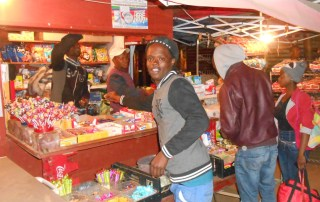 Julius Sematla, pictured, built a successful business from selling candy. Seen here in front of his candy kiosk. Photo/ILO