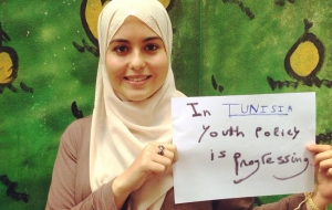 """A young woman in a headscarf holds up a sign that says """"In Tunisia, youth policy is progressing"""""""
