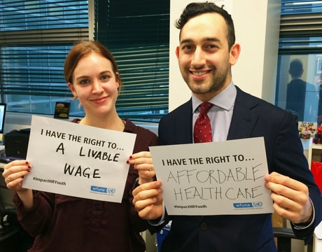 A photo of two young people holding signs for the #ImpactHRYouth campaign