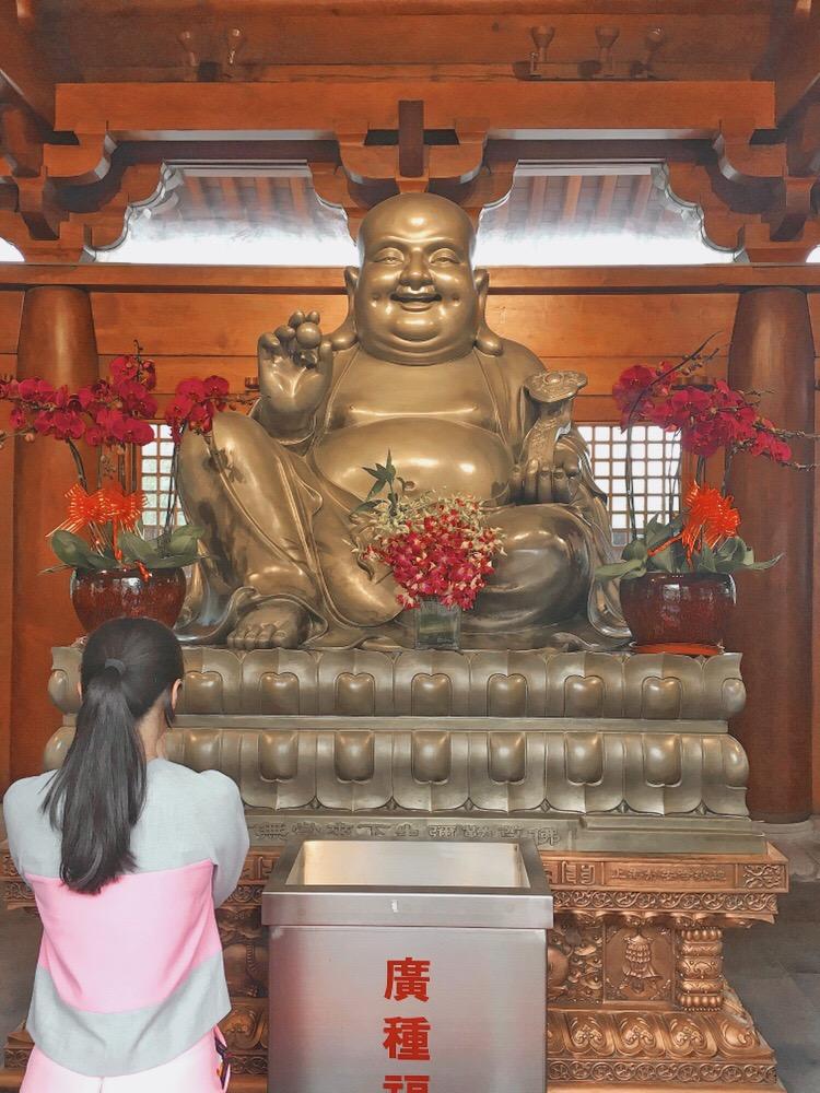 Ragazza in preghiera nel tempio buddista di Jing'an a Shanghai