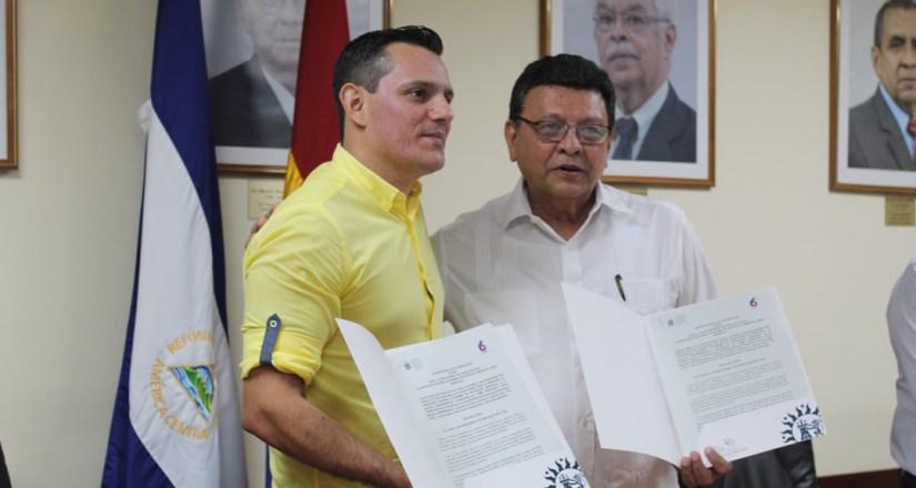 Representantes de ambas instituciones muestran el convenio, una vez realizada la firma.