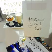 New piano book and grand piano bookmark as a well done for passing Grade 1 piano