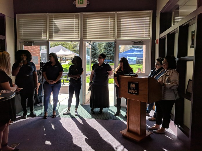 The Center for Women's and Gender Equity staff stand at the podium in the Scott-Willcoxon Hall.