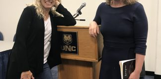 Lisa Zimmerman and Kasey Jueds pose for the camera next to a podium in the University Center
