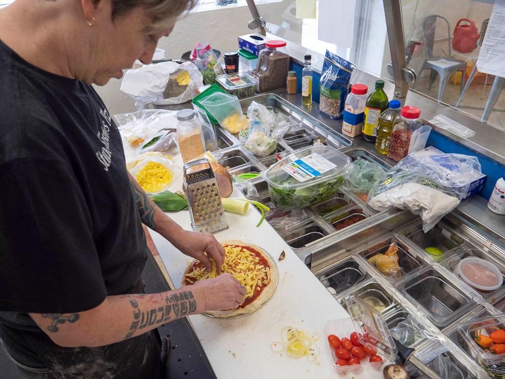 Preparing a pizza at Stone Sisters Pizza Bar - photo by Dennis Spielman