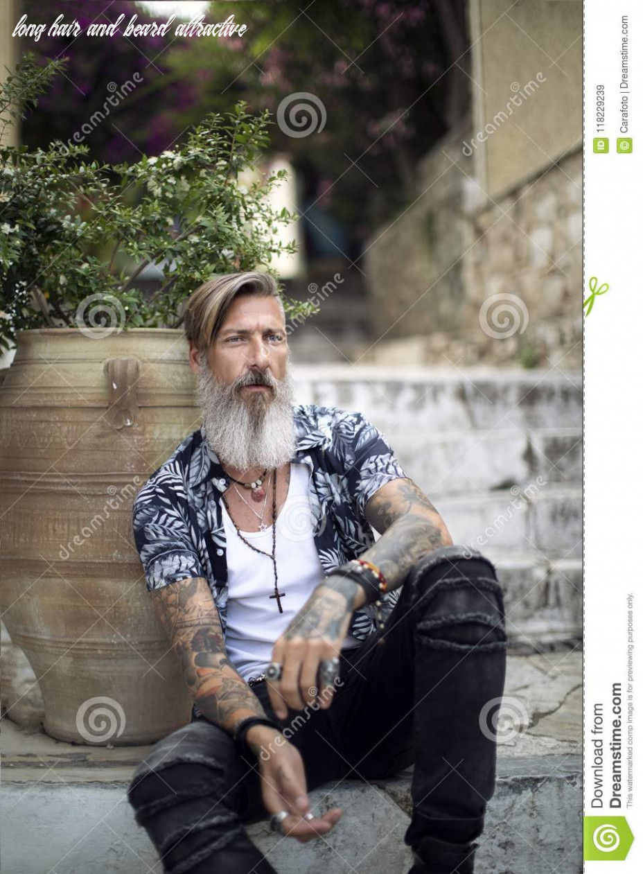 Attractive man with a beard and tattoos is sitting on the
